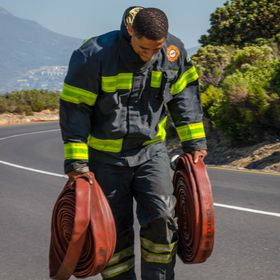 This was taken on day 3 of a terrible fire that ravaged the Western Cape mountains in Cape Town in March. This photo is of a fireman carrying hoses.
