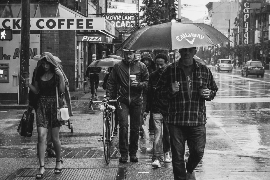 A street scene of Vancouverites walking in the rain on Granville Street.