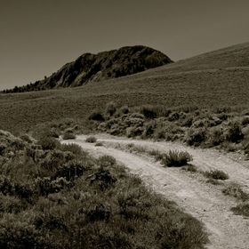a black and white photo of rural road in the foreground and Delaney Butte above.