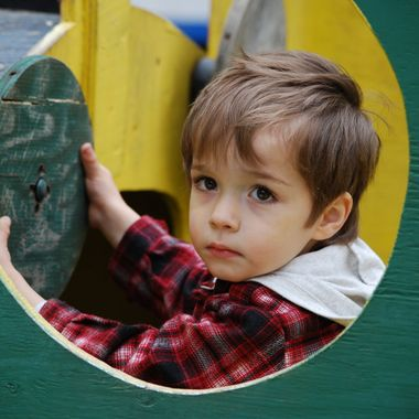 little boy playing in old wooden train in campsite playground in Coombs