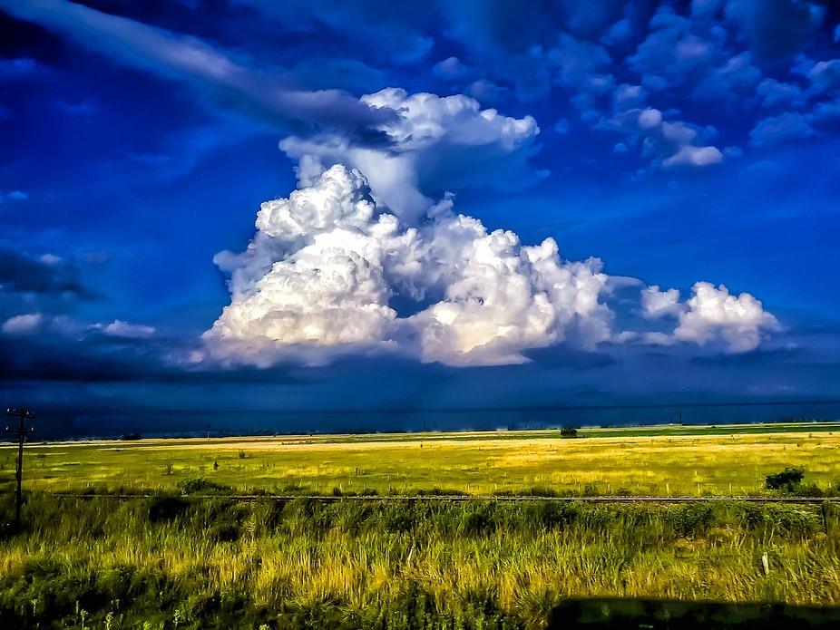Un campo y sobre él una gigantesca nube blanca en ell azul del cielo.
