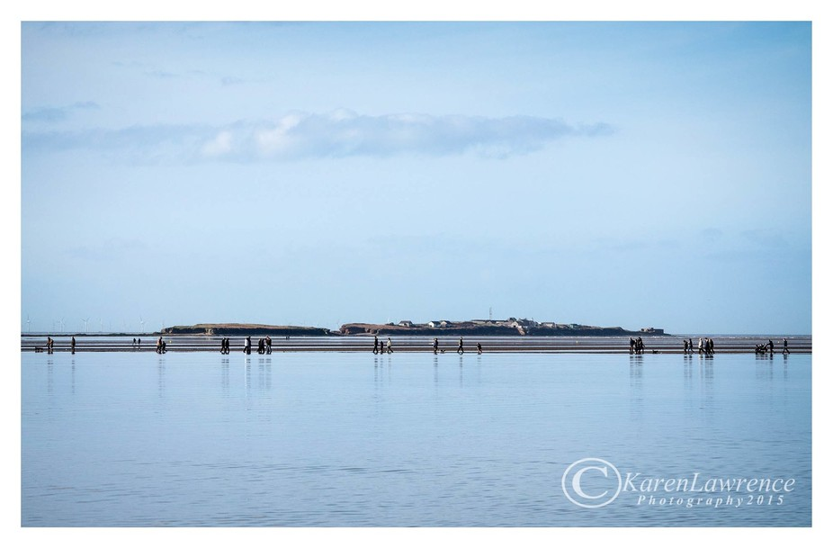 Looking out over the marine lake to Hilbre island, people look like they are walking on the water...