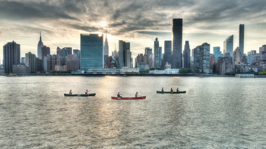 Row boats pass as the sun sets behind Manhattan.