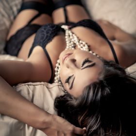 A beautiful brunette laying on a bed in black lingerie