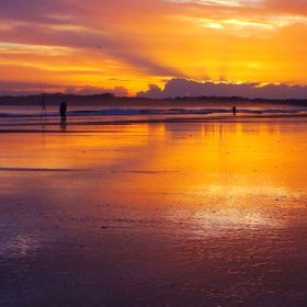 The bright sunrise sky reflecting off the wet sand on East Beach, New Zealand.