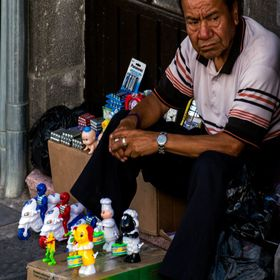 Older man selling toys on the the streets of Puebla.