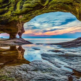 The sunset sky over Lake Superior is photographed from within a secluded sea cave along Michigan's Upper Peninsula coast near Munising.