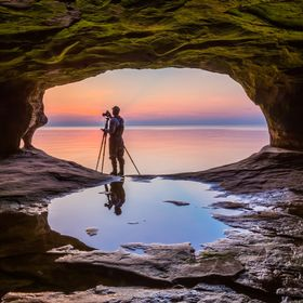A photographer with tripod is silhouetted against a sunset sky over Lake Superior as photographed from within a small sea cave on the coast of Up...