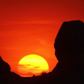 Sunset in Phoenix, Arizona, from The Hole In the Rock in Papago Park.  You can see three people sitting there, one sun center and the other two i...
