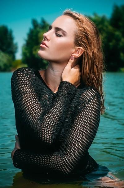 Beautiful girl enjoying the sun while posing in a lake
