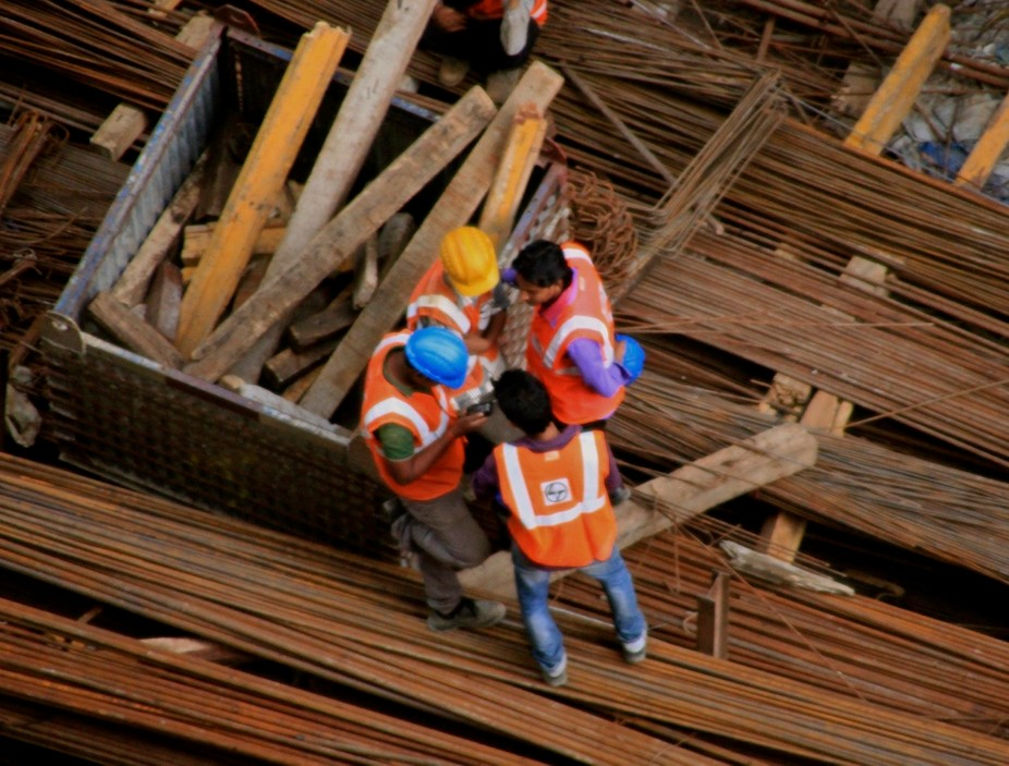 Workers at a construction site take a break as they peer into a co worker's phone.