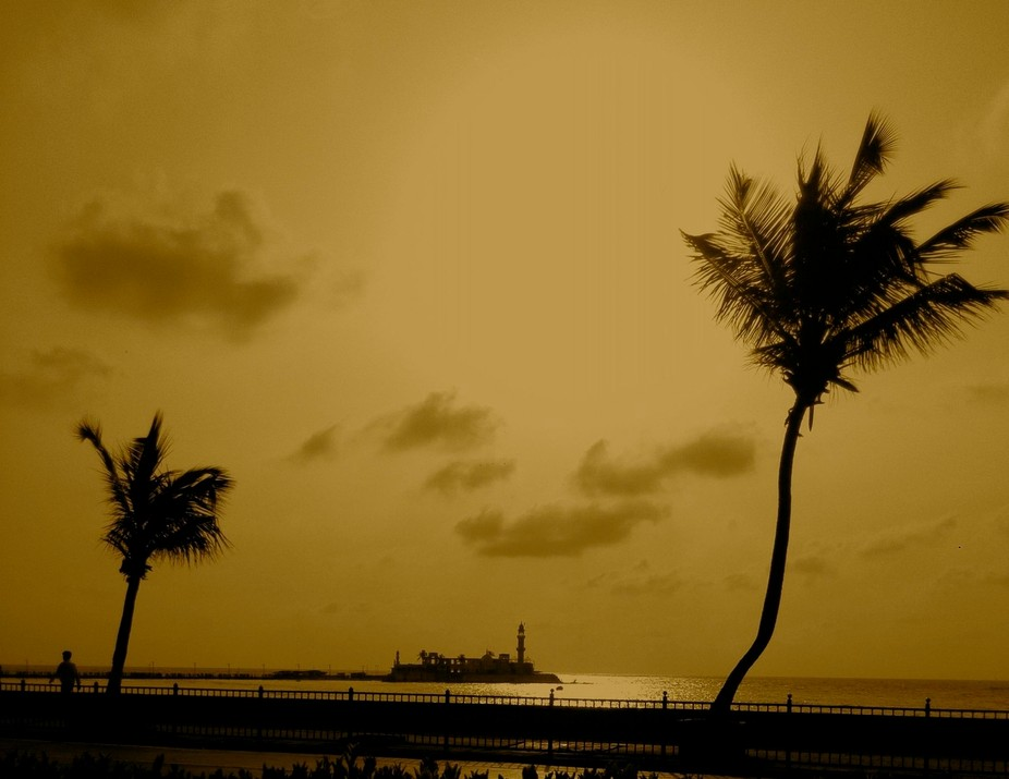 The famous shrine of Haji Ali in Mumbai at sunset, flanked by two palms trees.