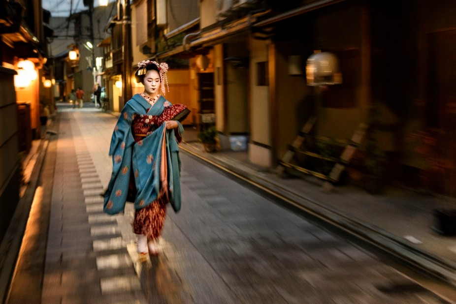 Early evening in Miyagawa-Cho Geisha district, Fumiyoshi, a Maiko, walks down the main street on ...