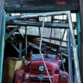 An old firetruck store in a barn falling apart