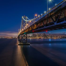 San Francisco-Oakland Bay bridge at night with San Francisco skyline at the background.