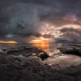The sun fights to shine it´s last rays of the day as it is being overpowered by dramatic rain clouds. Shot on the shores of Hvaleyri, Iceland.