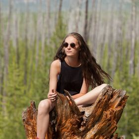 This woman was just sitting on this stump in Yellowstone, taking in all the beauty around her.
