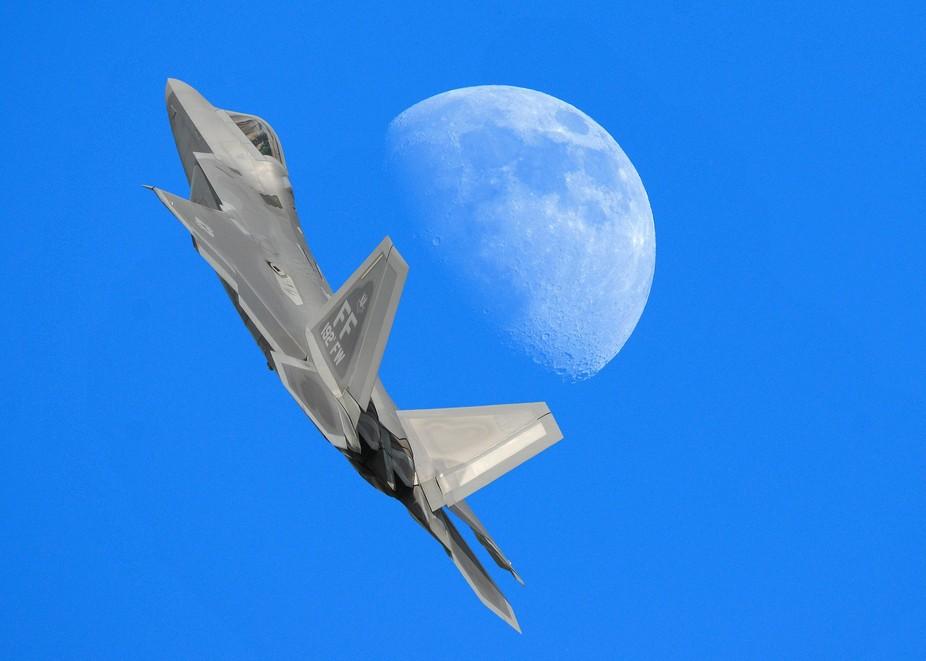 F-22 Raptor shooting past the moon over Oshkosh.