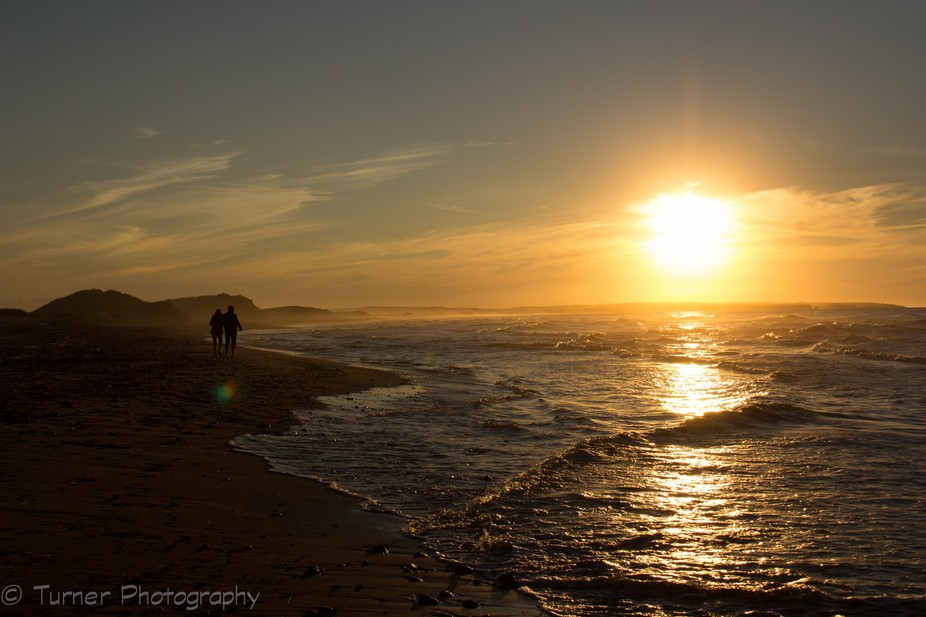 Taken at sunset with a couple walking along the beach