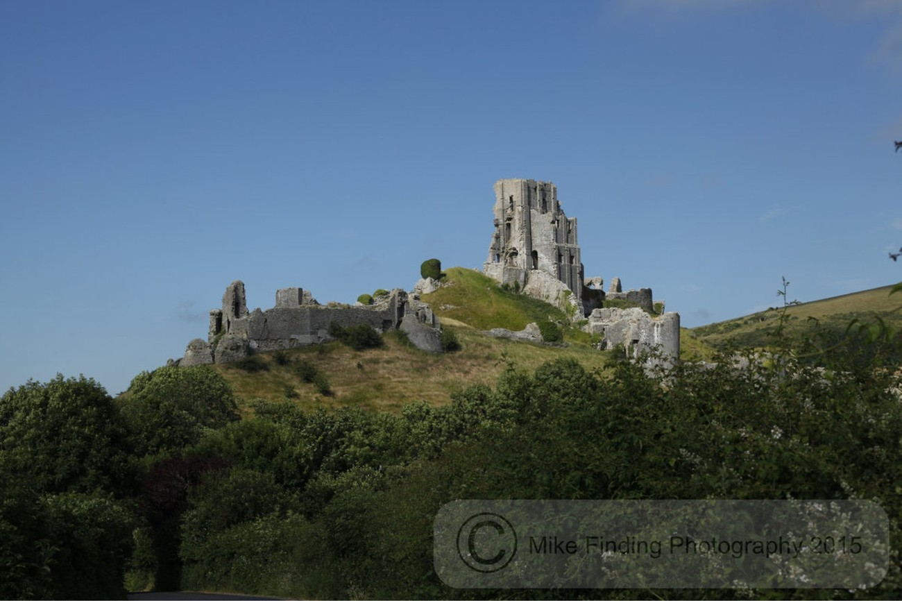 Corfe Castle is a fortification standing above the village of the same name on the Isle of Purbeck in the English county of Dorset.
