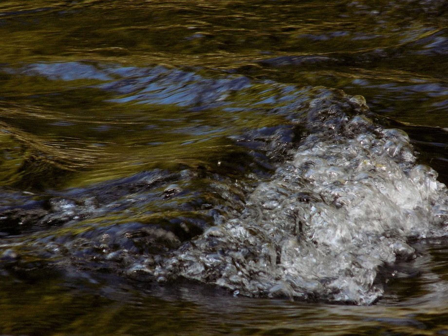 water going over rocks in a small creek off of a waterfall