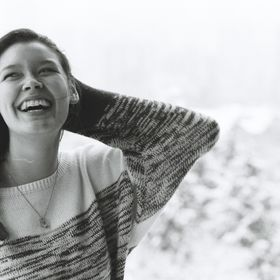 A black and white film photograph of a good friend smiling and lauhing