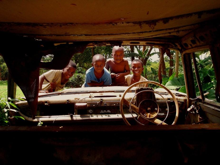 A group of children play at their backyard, with what is left of an old Mercedes at the suburbs o...
