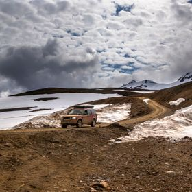 Journey through the interior of Iceland in a Landrover Discovery, dramitc sky and geothermal ground.
