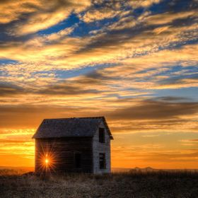 The setting sun peeks through the window in a long abandoned home on the South Dakota prairie.