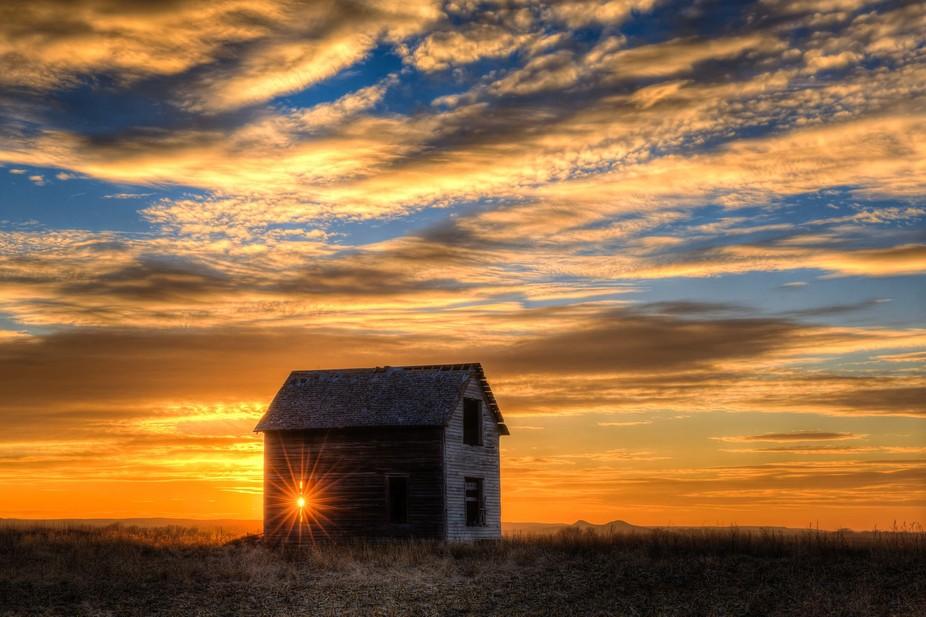 The setting sun peeks through the window in a long abandoned home on the South Dakota prairie.