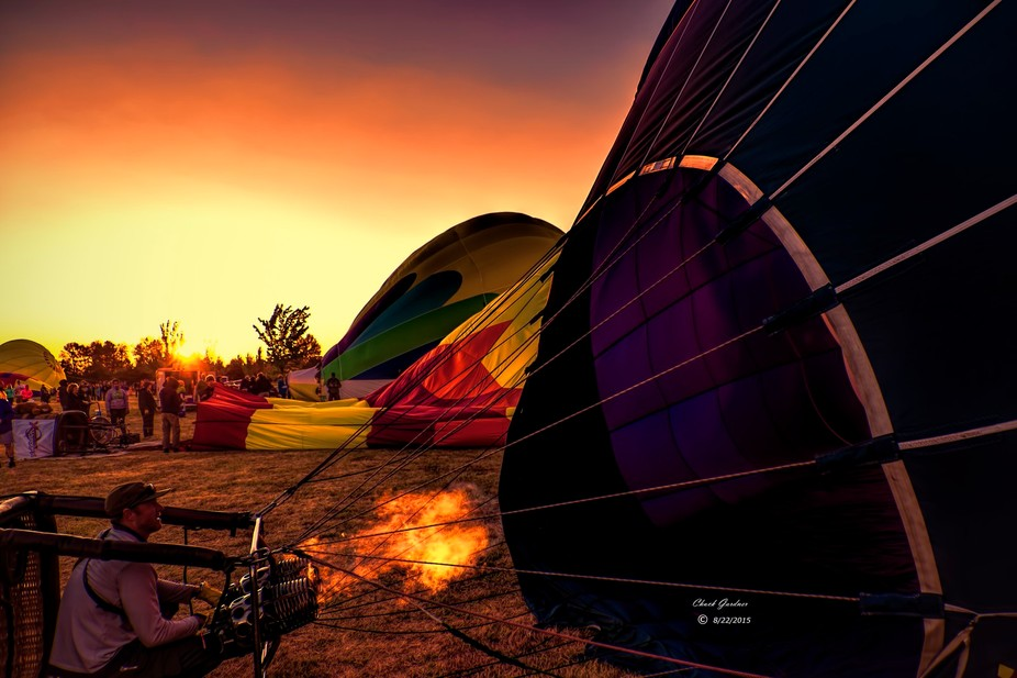 Hot air balloons getting ready for takeoff at sunrise.
