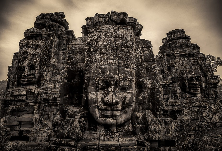 Ancient smiling faces carved in stone at Bayon Temple, Angkor Thom.  Siem Reap, Cambodia.