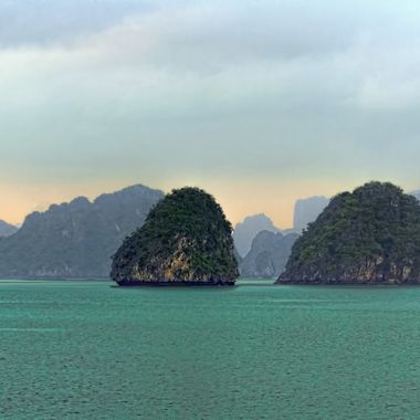 Ha Long Bay, Viet Nam is a world heritage site featuring rock formations that jut up from the beautiful aquamarine water.