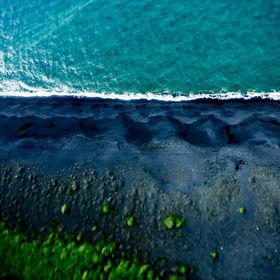 Aerial shot over Iceland of a black sand beach