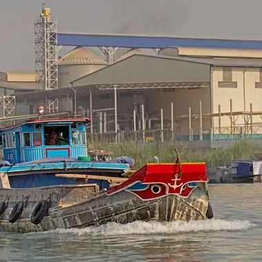 A Mekong River boat with typical eyes on its bow passes a rice processing factory.