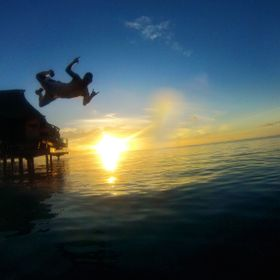 A man jumps into the ocean at sunset in Moorea, one of the French Polynesian islands