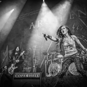 Arch Enemy on stage at the 2014 Copenhell metal festival in Copenhagen, Denmark. In the foreground lead vocalist Alissa White-Gluz and on the lef...