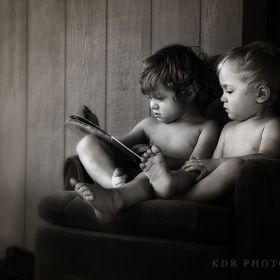 Teaching his little brother about the magic of books.