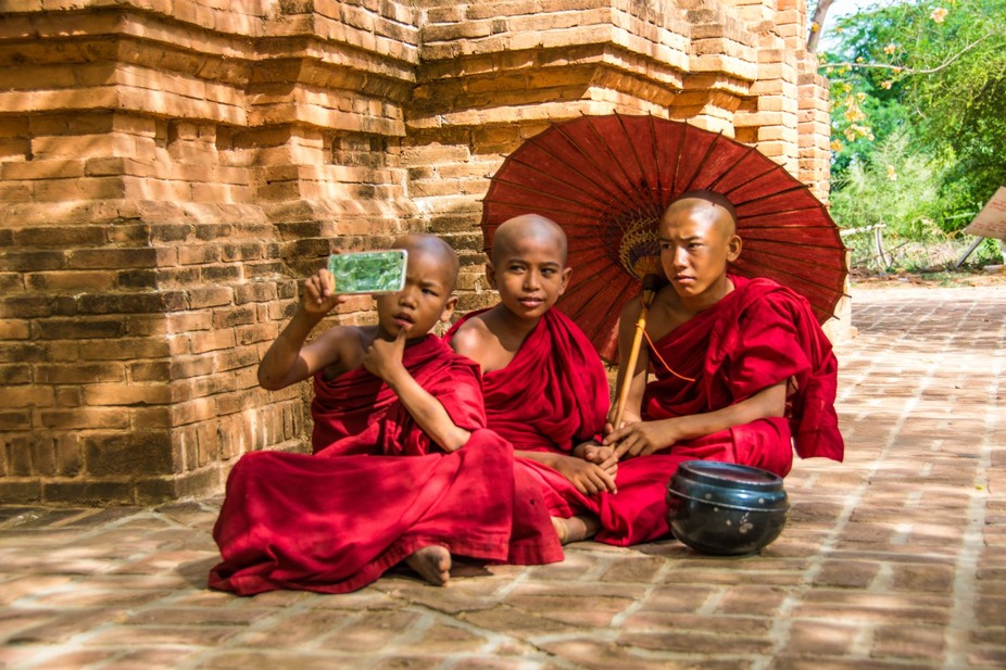 3 monks trying to take a selfie using a smartphone