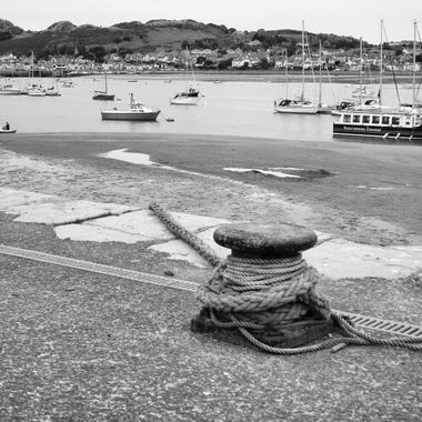 Conwy quayside in North Wales celebrates its fishing industry, past and present. Here a hawser stretches from a bollard to a boat at low tide.