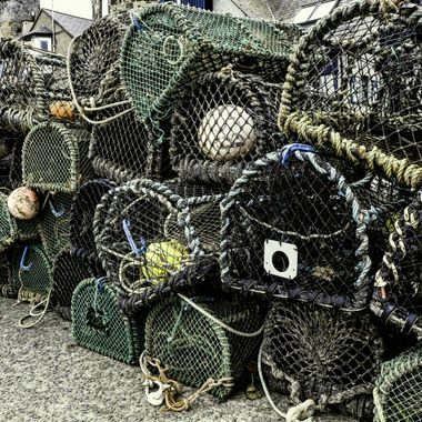 Conwy quayside in North Wales celebrates its fishing industry, past and present, here is a stack of lobster pots on the quayside awaiting deployment on the high tide.