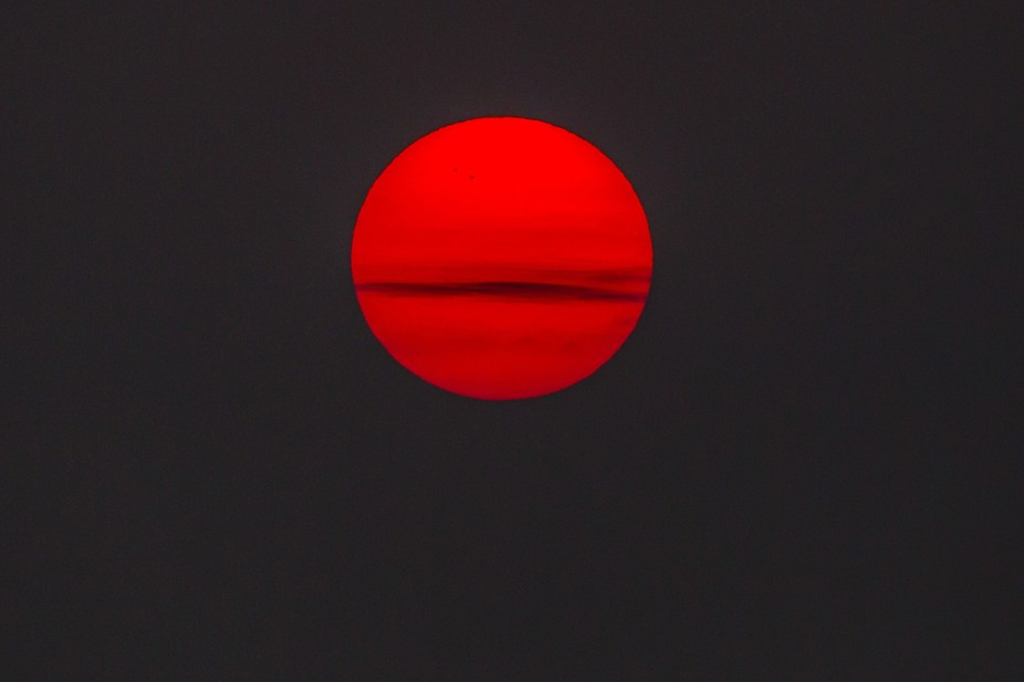 early morning shot of rising sun with some clouds makes this look like a much larger planet - can...