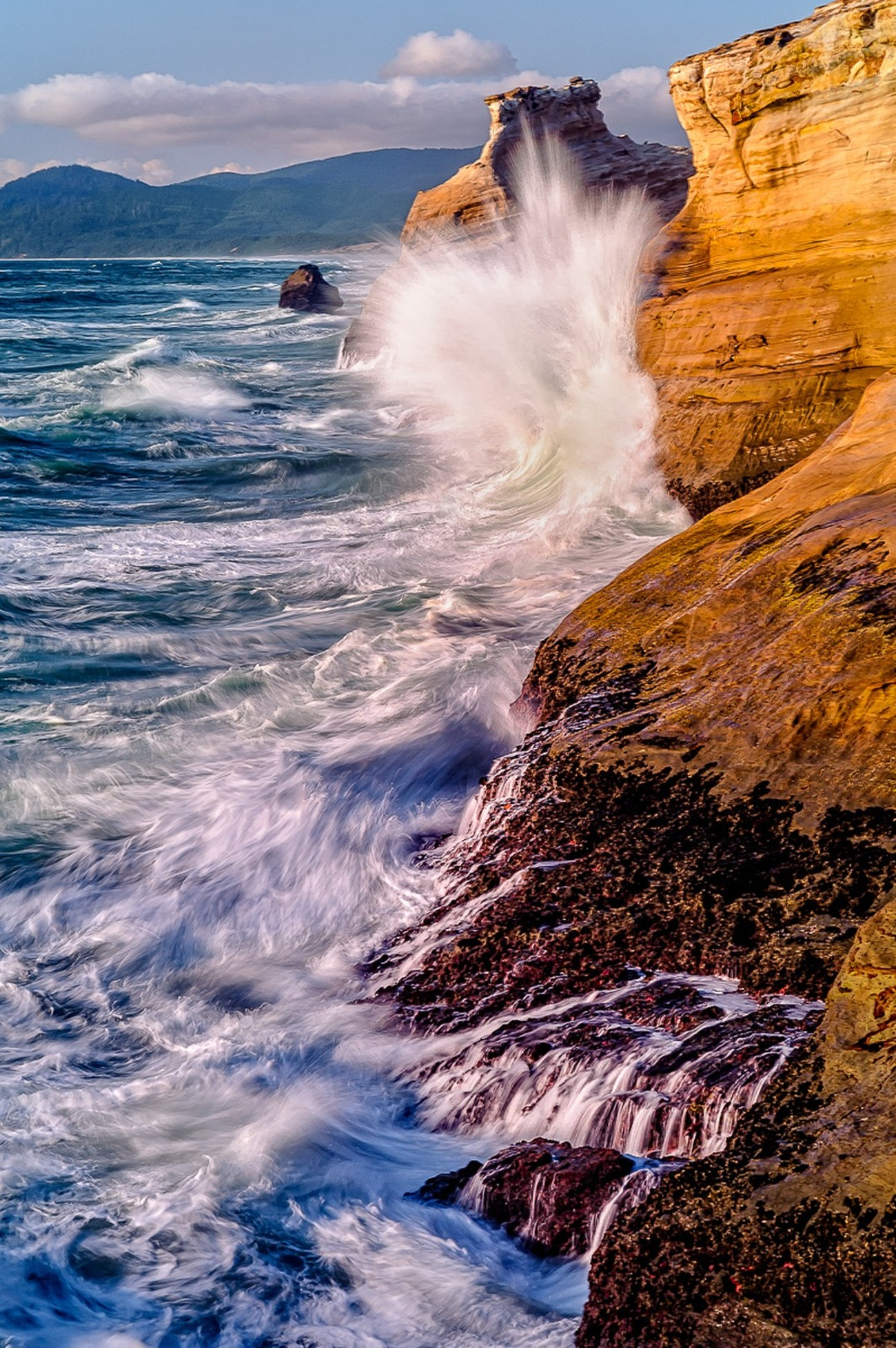 This image was captured about 45 minutes before sunset at Cape Kiwanda near Pacific City on the Oregon northern Coast. It was captured using a slow shutter, a Singh Ray graduated neutral density filter, and a tripod with mirror up and a shutter release cable. Over 170 photos were taken in this series in order to capture 7 of waves crashing at the desired height. Nikon D700, 24-120 lens, ISO 100, 78mm, .4 sec, f/14, manual exposure, matrix metered.