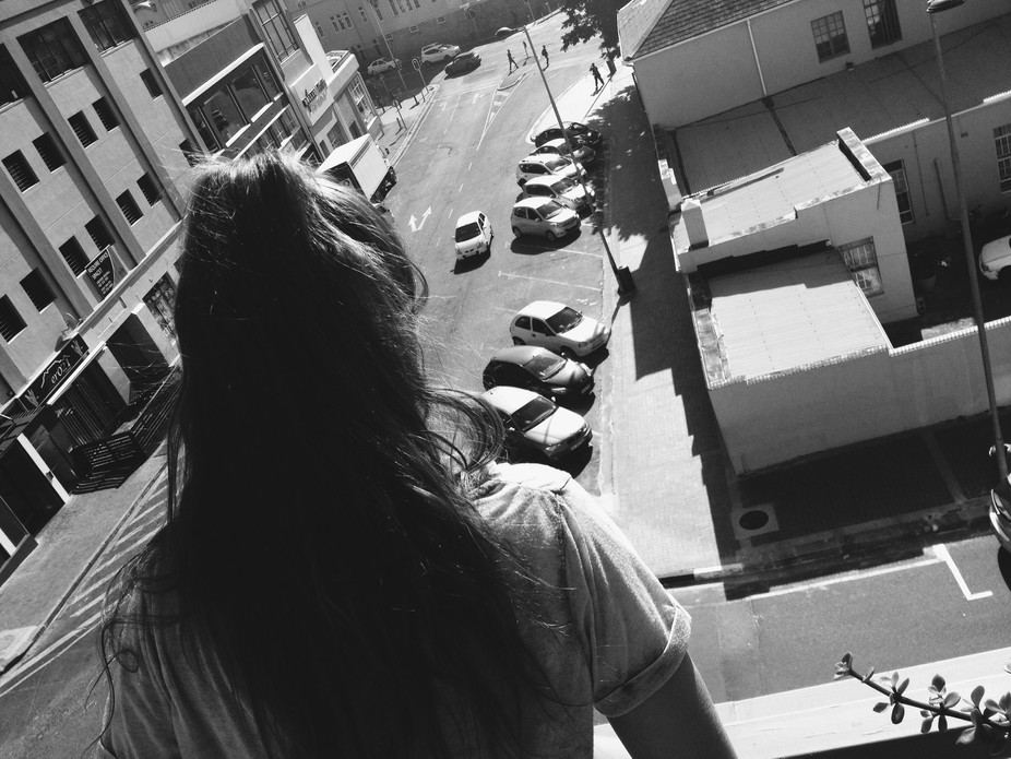 I took this picture of my friend looking down onto the street while were on the roof of a building.