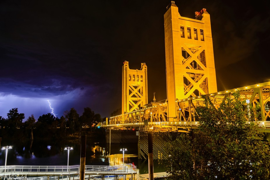 Sacramento's Tower Bridge with a bit of lightning behind it during a thunderstorm