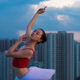 Shortly after sunset Ding Chan, a Chinese office worker, poses atop a 14th floor rooftop in Beijing, China. Her regular classic ballet classes ar...