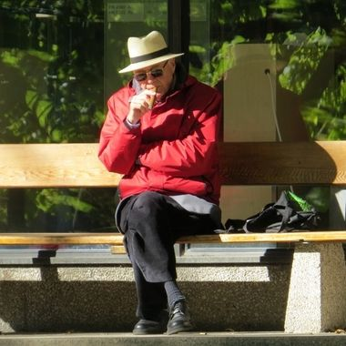 A man sits on a bench and pensively smokes a cigar.