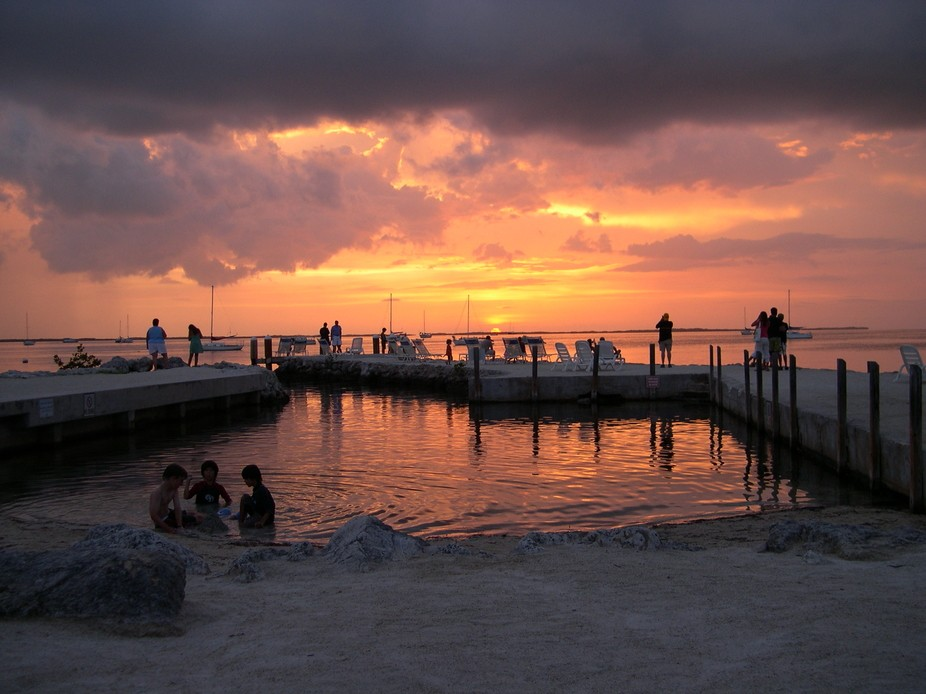 A Florida vacation spot with beautiful sunsets every evening. Our 2 boys trying to catch minos wi...