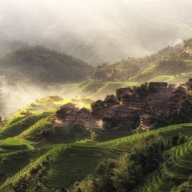 Sunrise light through the hills of Longji rice terrace in guangxi province, China. The village perched on top is Tiantouzhai. Watching the sunray...