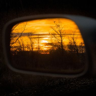 Side mirror of a car, reflecting the sunrise behind me.